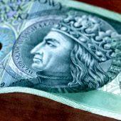 Banknot stuzłotowy z wizerunkiem króla Władysława II Jagiełły. W tle po jego obu stronach znajdują się stylizowane elementy ornamentyki gotyckiej.