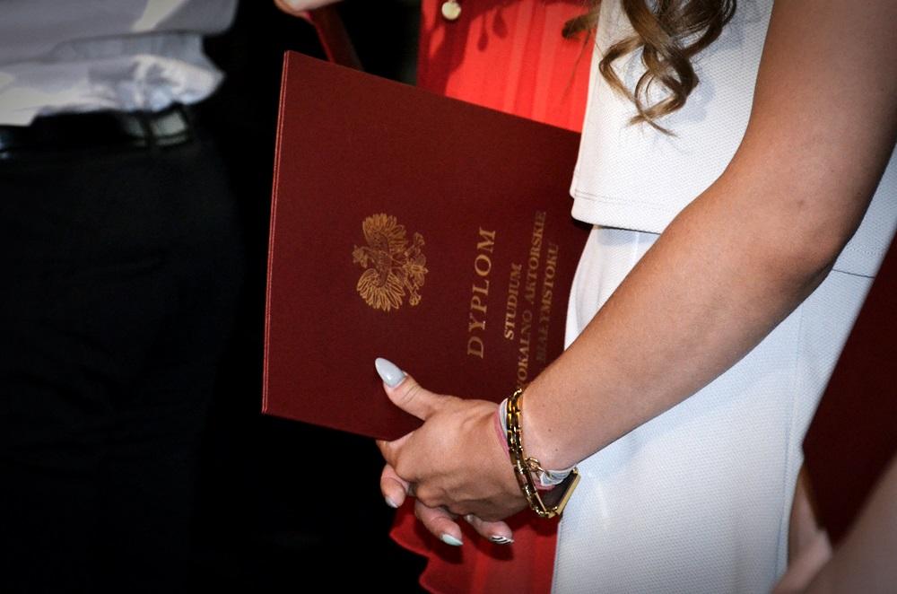 Uczennica w białej sukience trzyma dyplom