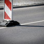 Biało-czerwony pachołek na drodze informujący o utrudnieniach w ruchu.