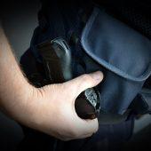 Policjant trzyma rękę na kaburze, w której jest broń
