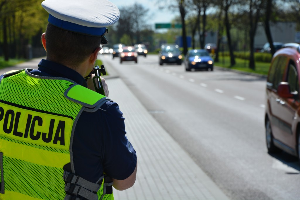 Policjant mierzy prędkość przy ruchliwej ulicy