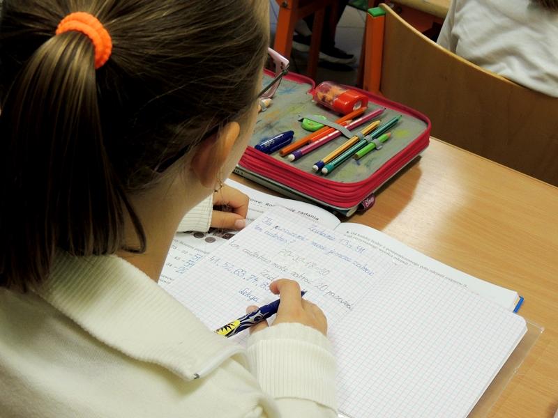 Uczennica siedzi w ławce i pisze w zeszycie. Na ławce, oprócz zeszytu, leży też piórnik