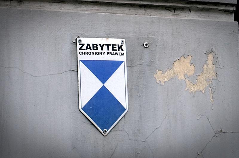 Obdrapana ściana budynku, na której wisi tabliczka z napisem zabytek