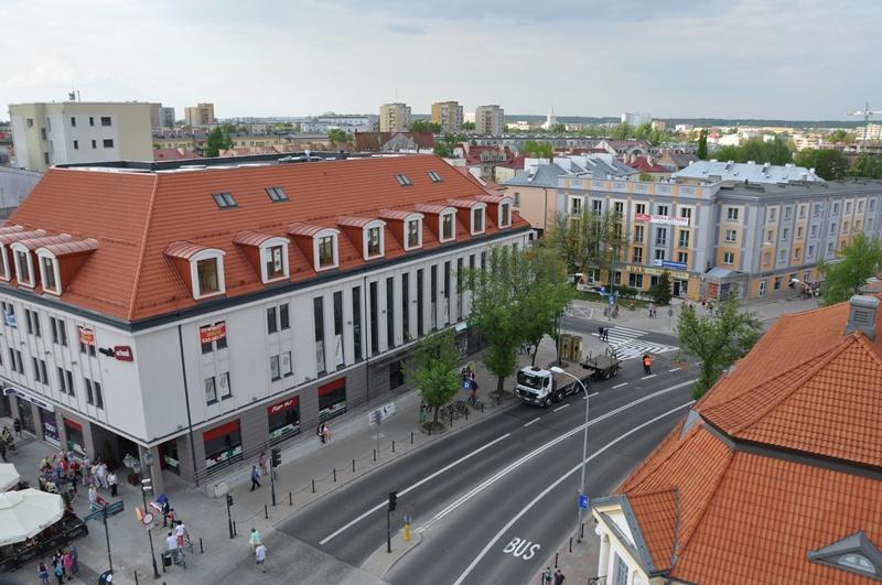 Ulica w centrum miasta, po obu stronach drogi kamienice