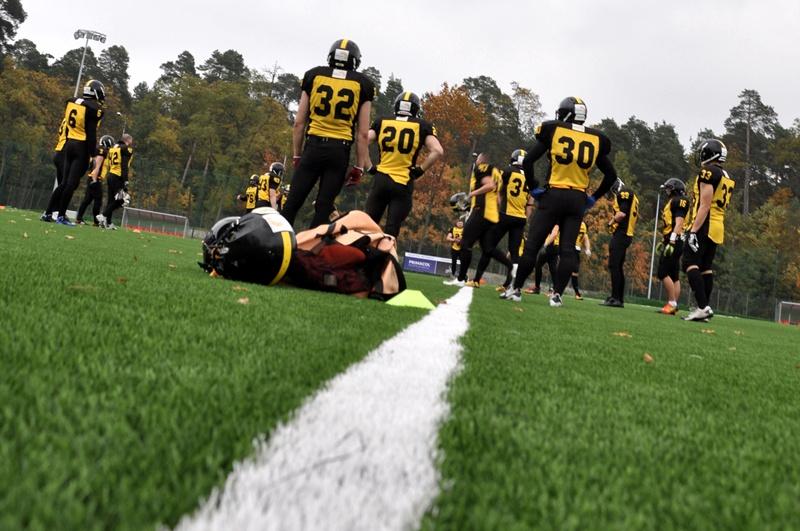 Zawodnicy futbolu amerykańskiego stoją na murawie stadionu