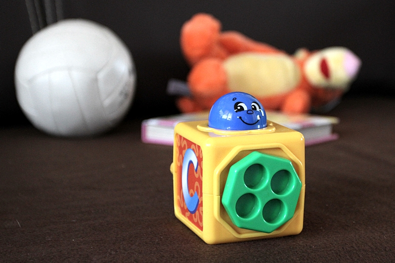 Na podłodze rozrzucone zabawki, maskotka i piłka