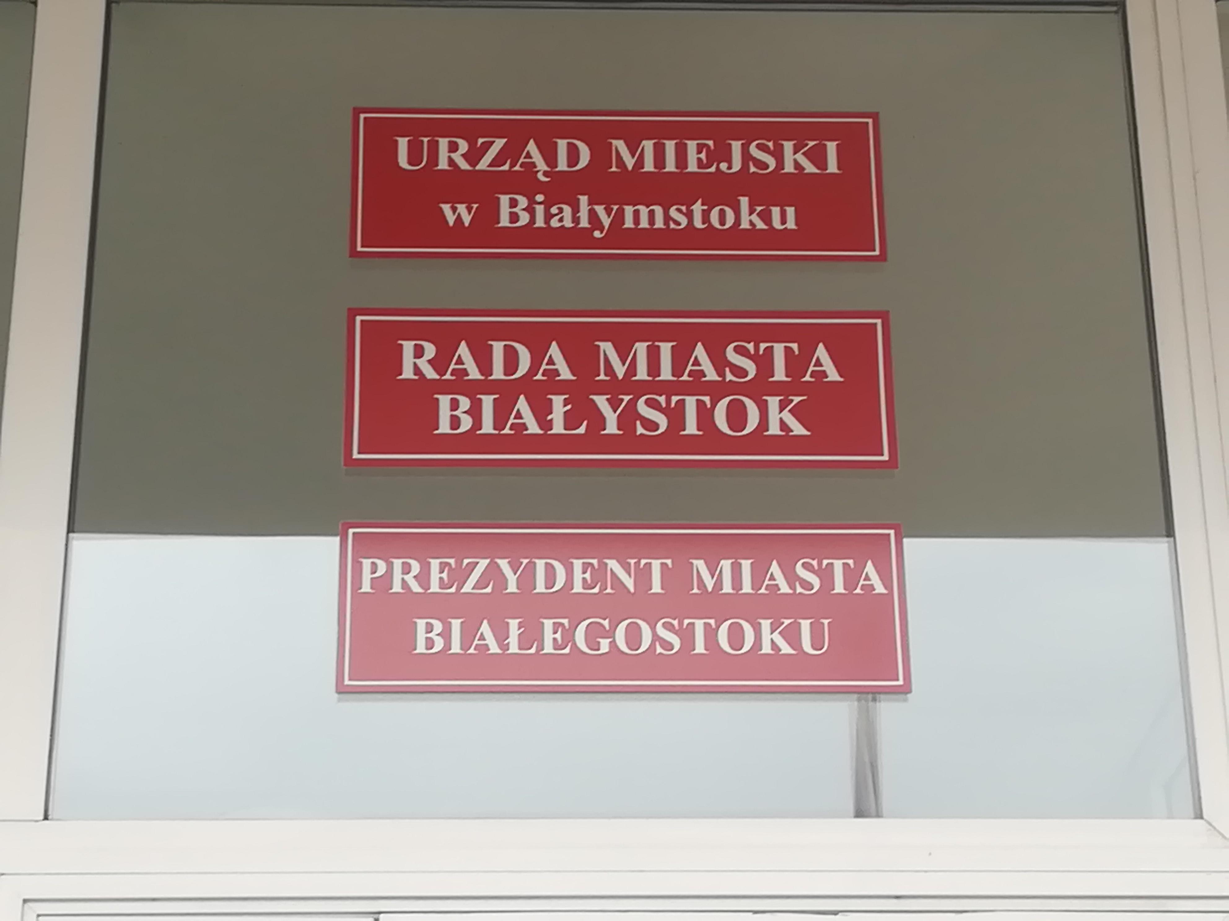 Trzy czerwone tabliczki na drzwiach budynku magistratu. Na pierwszej napisano Urząd miejski w Białymstoku, na drugiej - Rada Miasta Białystok, a na trzeciej - Prezydent Miasta Białegostoku
