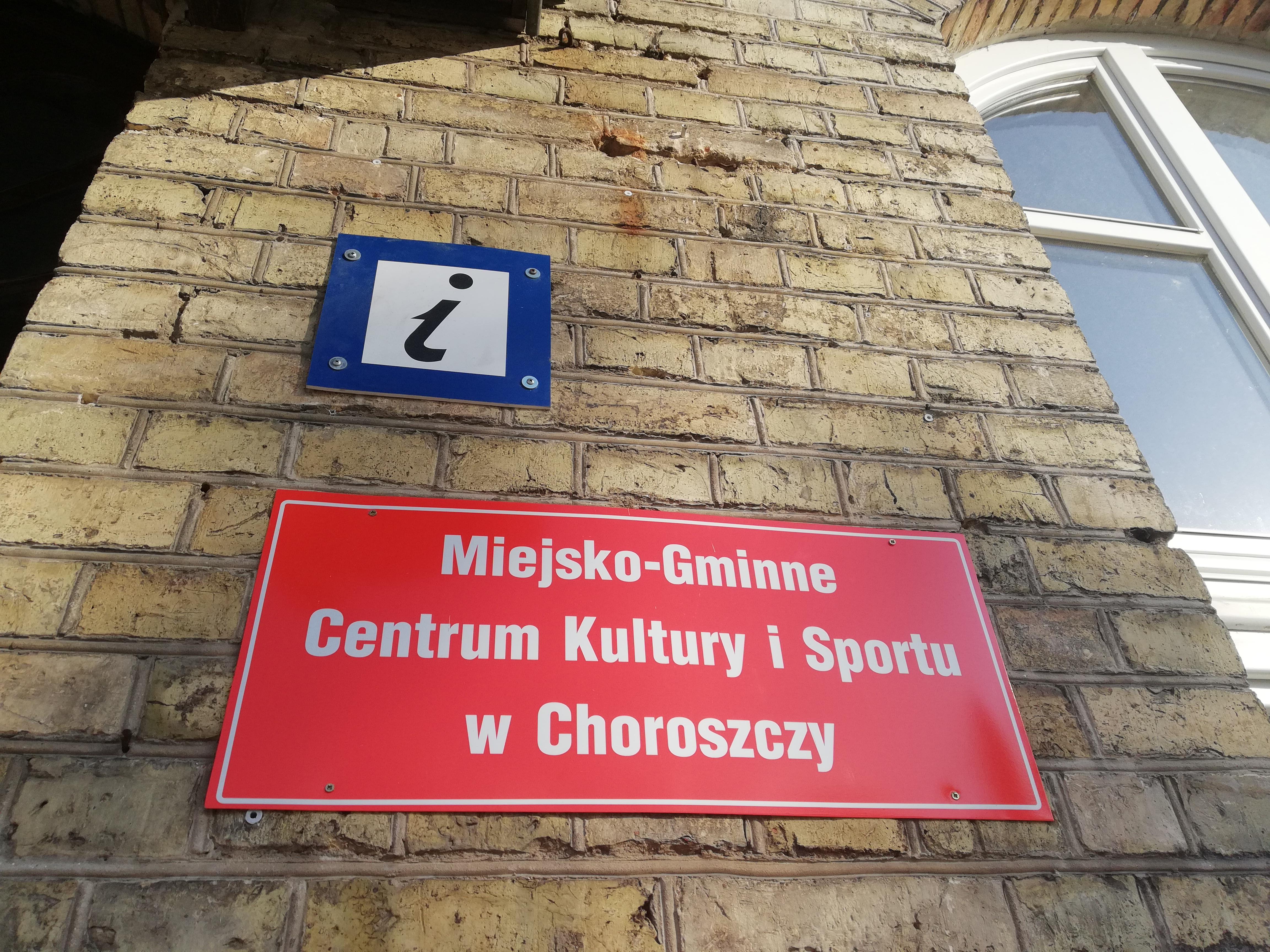 Tabliczka przed wejściem do budynku z napisem Miejsko-Gminne Centrum Kultury i Sportu w Choroszczy