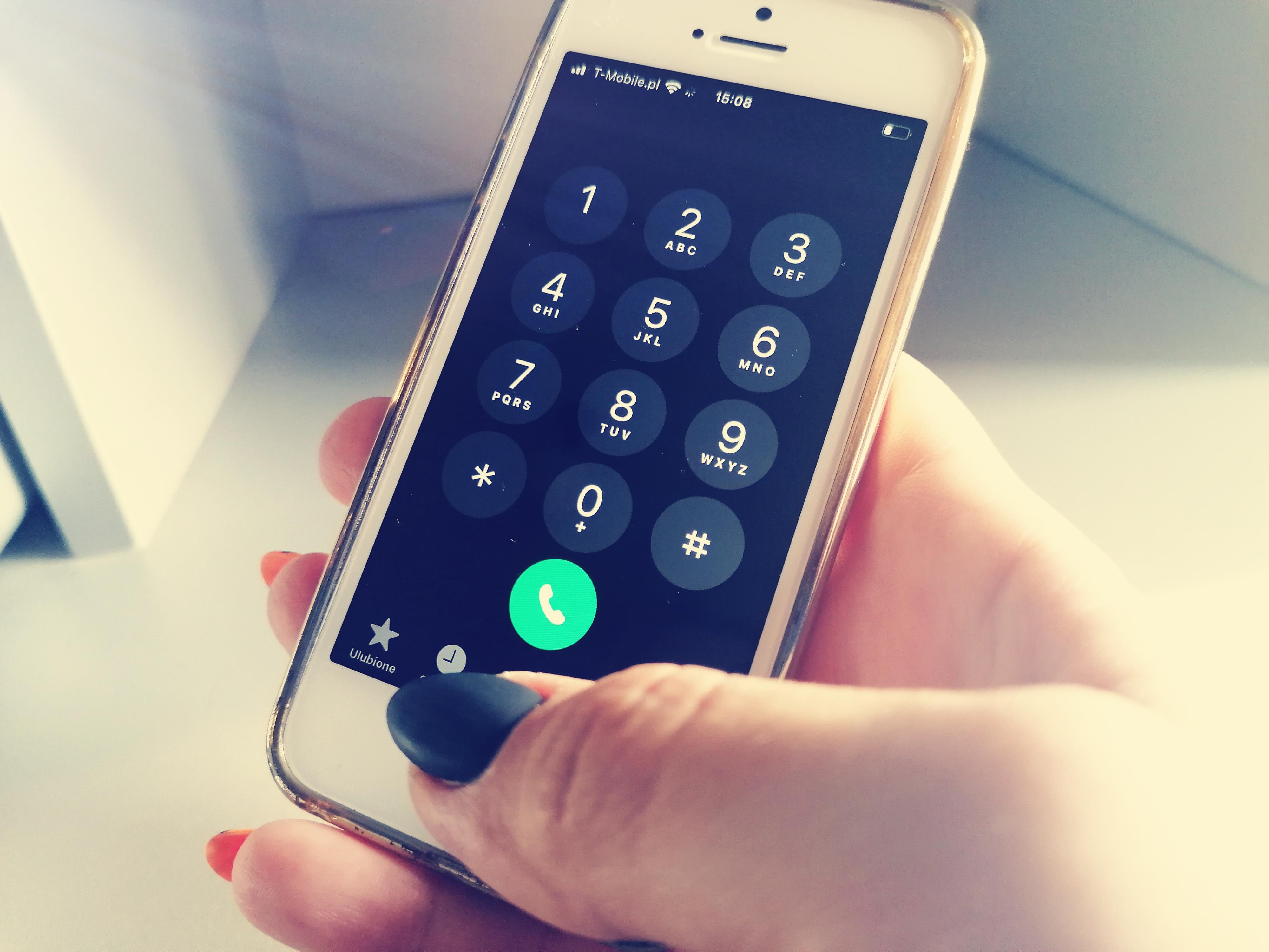 Biały telefon komórkowy trzymany jest w dłoni