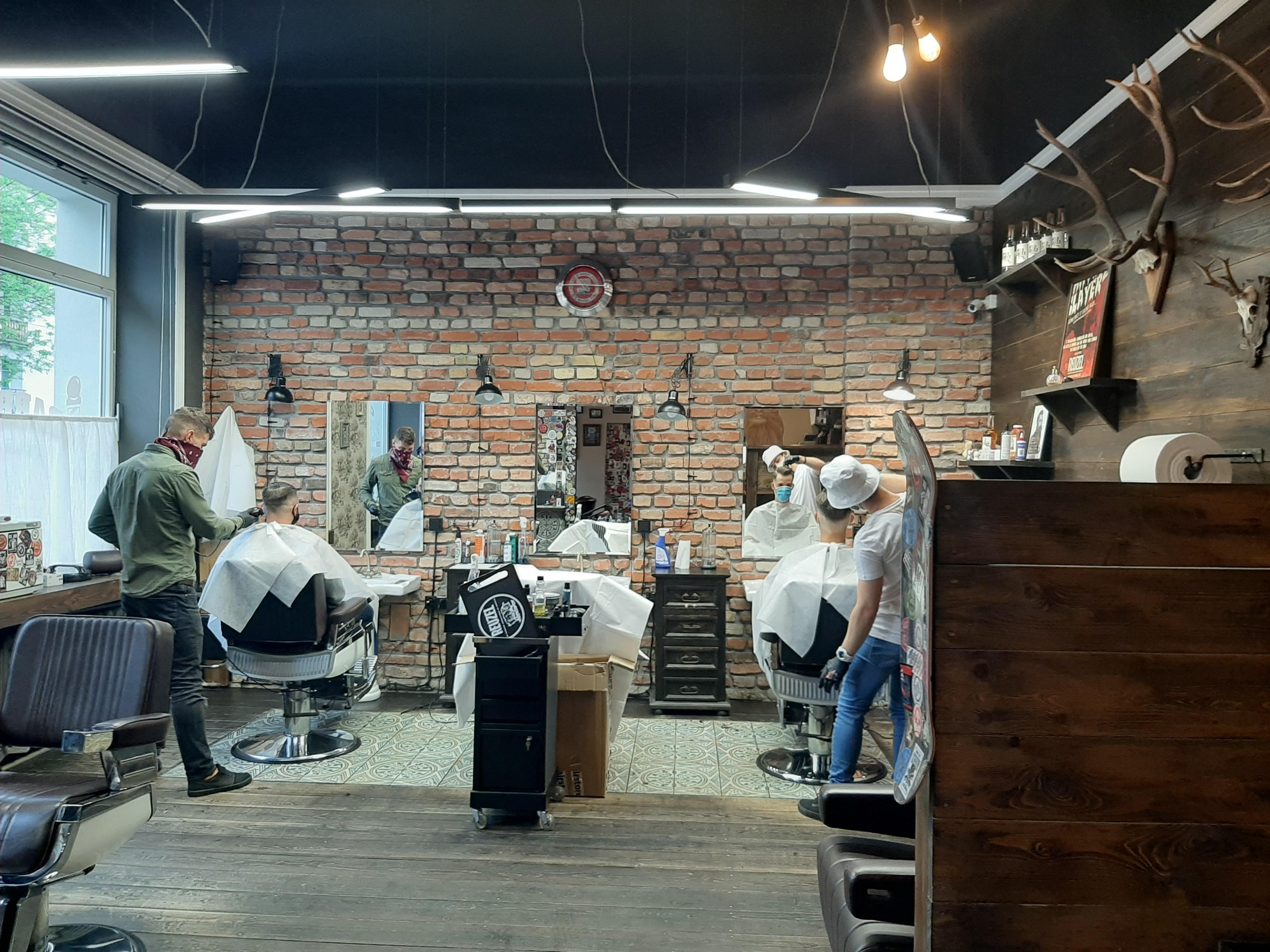 Mężczyźni siedzą na fotelach w salonie barber