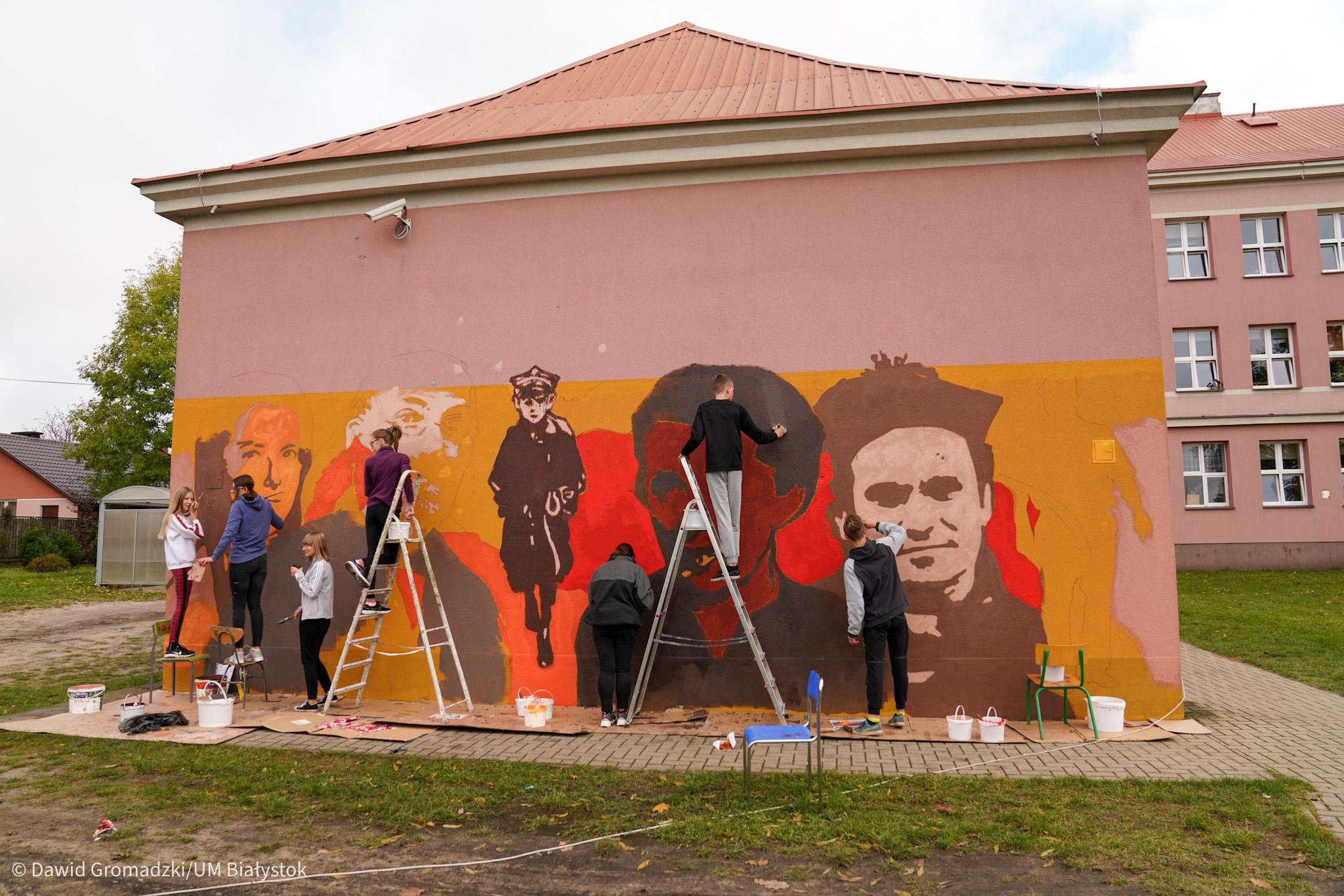 grupa młodzieży maluje mural na ścianie budynku