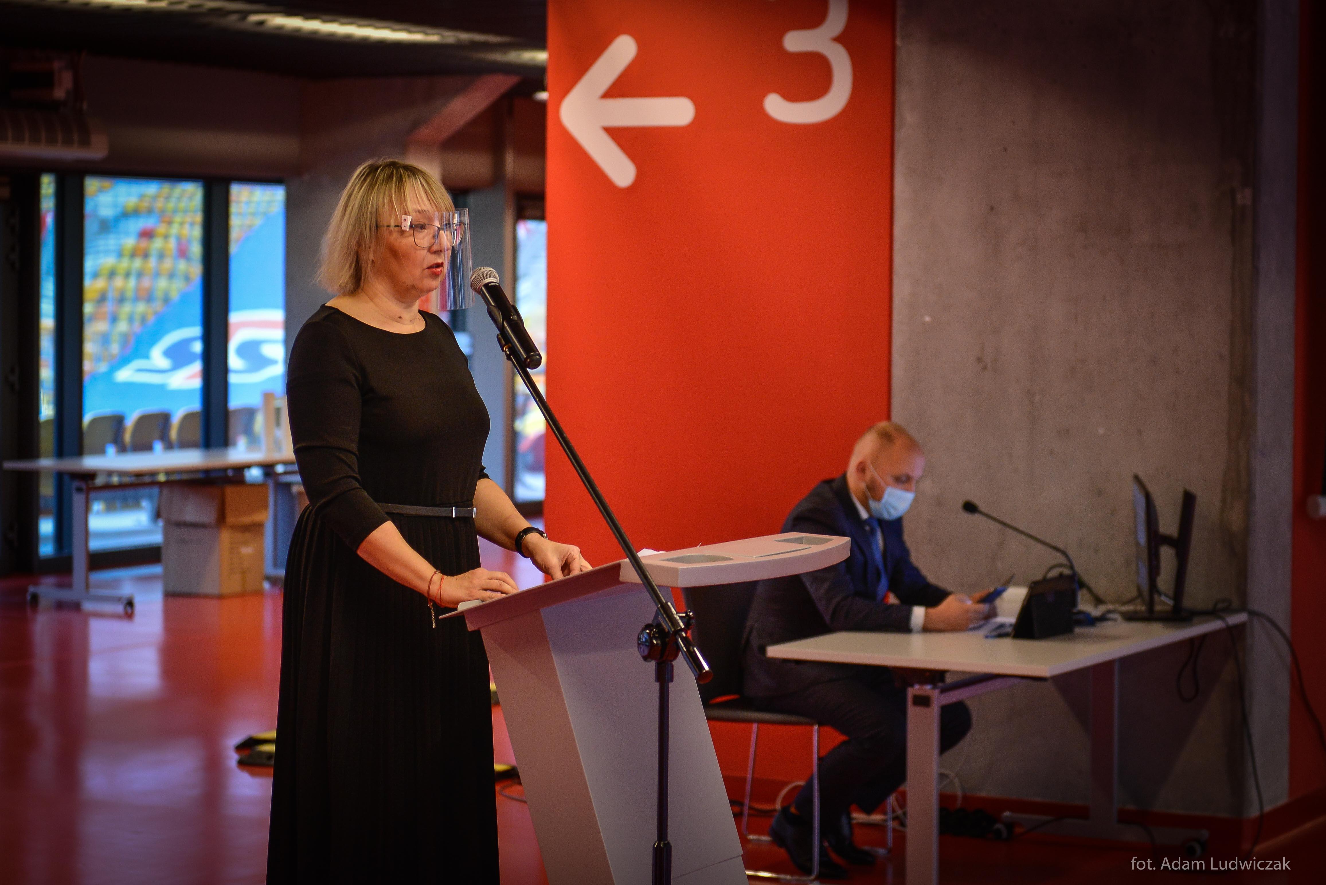 Kobieta w przyłbicy stoi na mównicy
