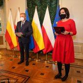 Po lewej stronie stoi prezydent Białegostoku . Za jego plecami są ustawione flagi Polski oraz Białegostoku. Po prawej stronie w czerwonej sukience stoi rzeczniczka prezydenta. Sytuacja ma miejsce w sali Pałacyku Gościnnego