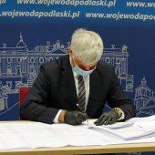 Wojewoda pochylony nad planami rozbudowy tras kolejowych podpisuje pozwolenie na kolejną rozbudowę odcinka. Wojewoda jest ubrany w czarny garnitur, za nim niebieska ścianka promocyjna Podlaskiego Urzędu Wojewódzkiego w Białymstoku