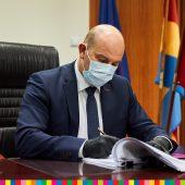 Marszałek Artur Kosicki siedzi przy biurku w masce i podpisuje dokumenty