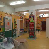 Klinika rehabilitacji dziecięcej w trakcie remontu. Ściany są w intensywnych, ciepłych kolorach. Na lewej ścianie jest namalowany zielony Shrek, brązowy zamek, na słupku na środku korytarza namalowana jest Fiona - żona Shreka. Po lewej stronie na pierwszym planie znajdują się puszki z farbami. W oddali wisi girlanda z kolorowych chorągiewek