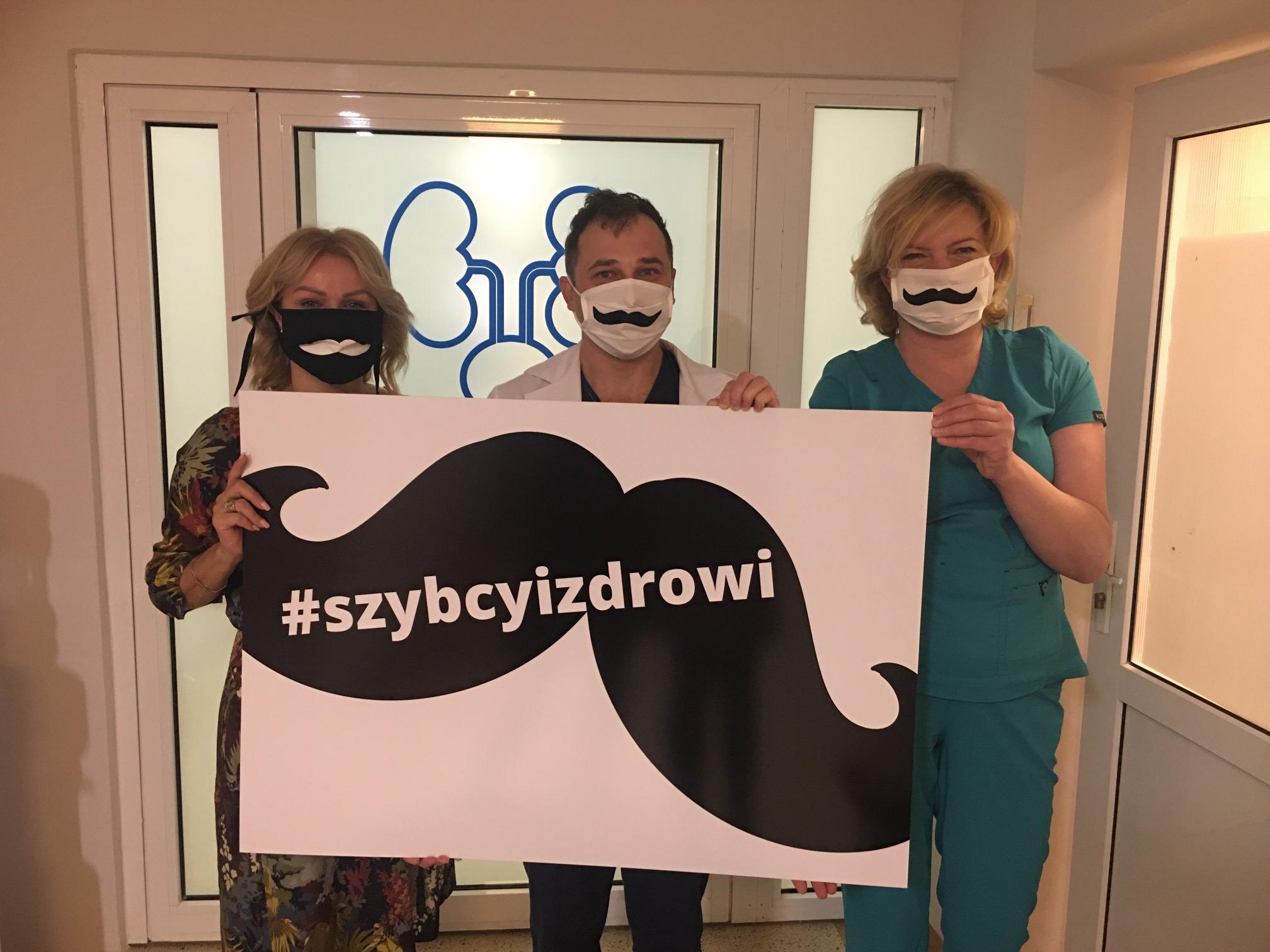 Trzy osoby trzymają plakat, na którym namalowane są czarne wąsy.