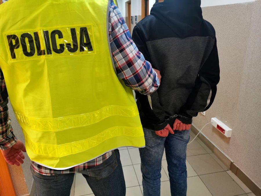 Policjant trzyma skutego kajdankami mężczyznę