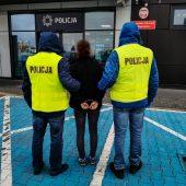 Policjanci trzymają skutą kajdankami kobietę
