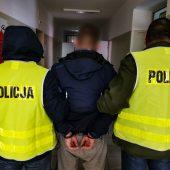 Policjanci trzymają skutego kajdankami mężczyznę