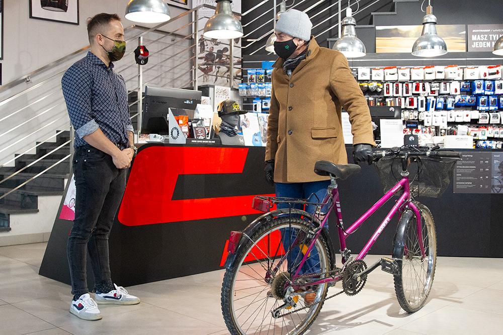 Dwóch mężczyzn znajduje się w serwisie rowerowym. Osoba z lewej strony jest ubrana w niebieską koszulę, czarne spodnie i białe adidasy. Mężczyzna z prawej strony jest ubrany w kurtkę w miodowym kolorze, granatowe spodnie. Na głowie ma szarą czapę i zasłonięte maseczką usta i nos. Osoba z prawej strony przekazuje na akcję charytatywną różowy rower