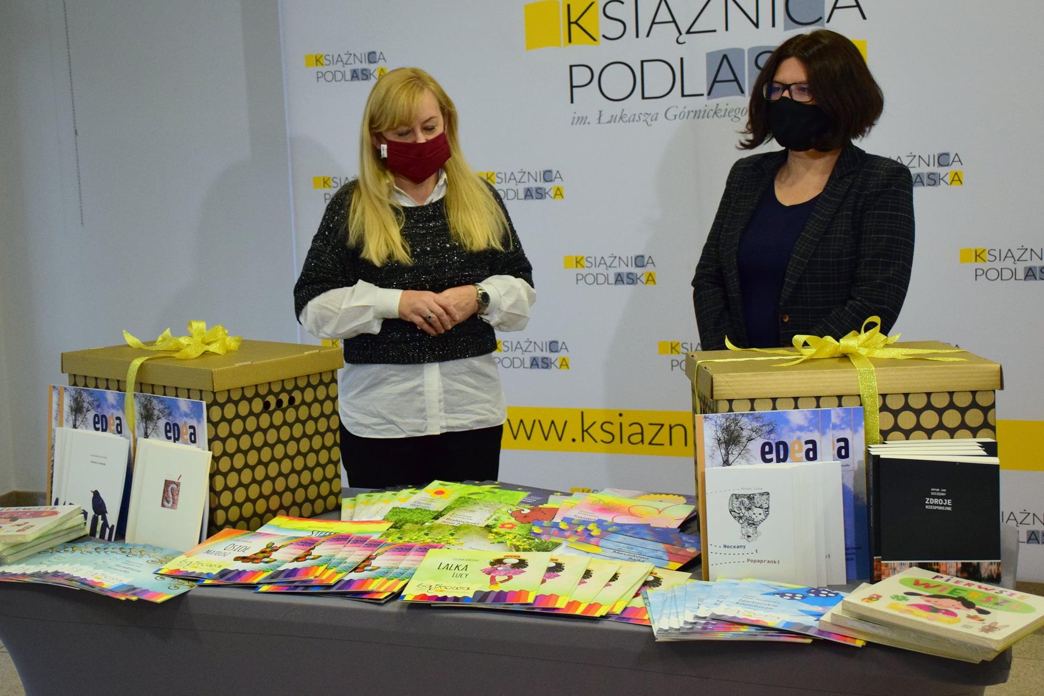 Dwie kobiety stoją za stołem, na którym ułożone są książki. Kobieta po lewej stronie ma długie, blond włosy i jest ubrane w czarne spodnie, białą koszulę i czarny sweterek. Kobieta po prawej stronie ma krótkie ciemne włosy, jest również ubrana na czarno. Za kobietami stoi baner z napisem Książnica Podlaska