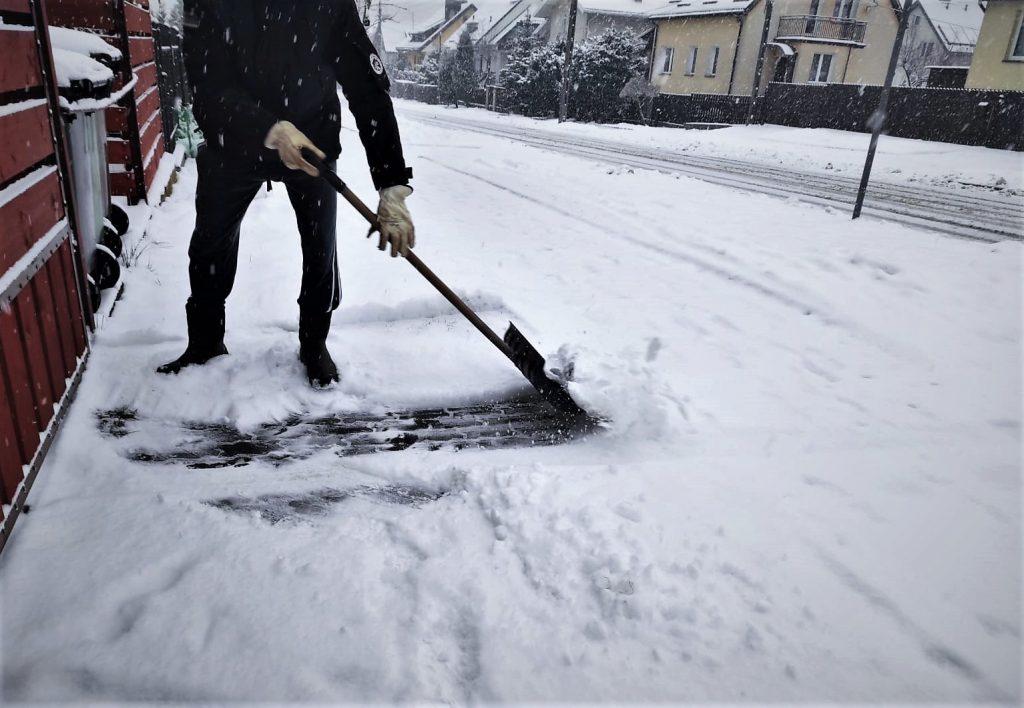 Mężczyzna odśnieża zasypany śniegiem chodnik