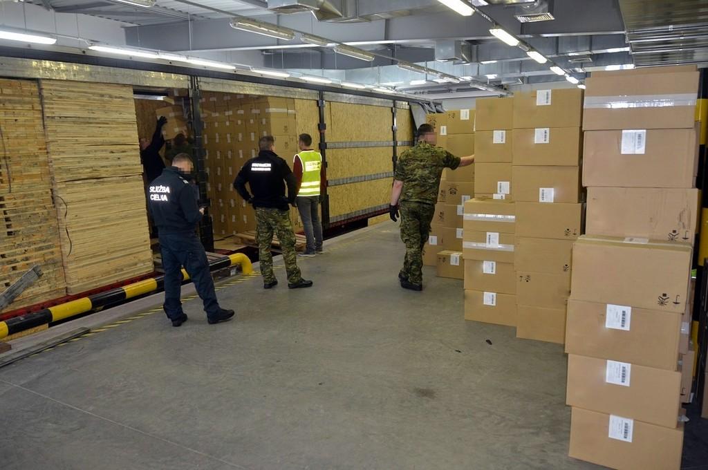 Funkcjonariusze przeglądają kartony z nielegalnymi papierosami