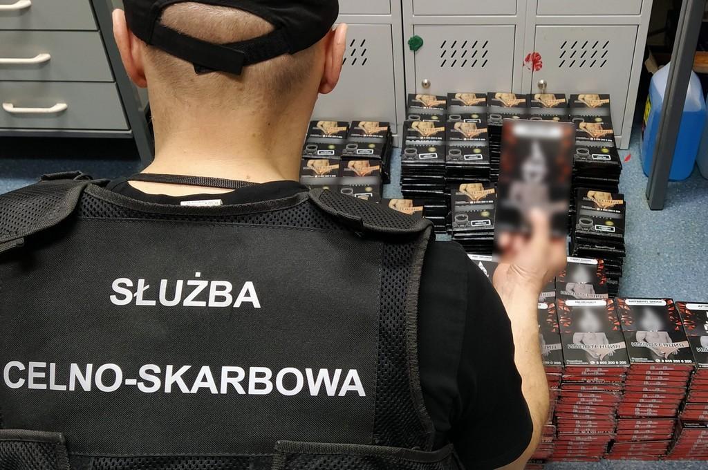 Funkcjonariusz KAS trzyma w ręku opakowanie z tytoniem do fajek wodnych