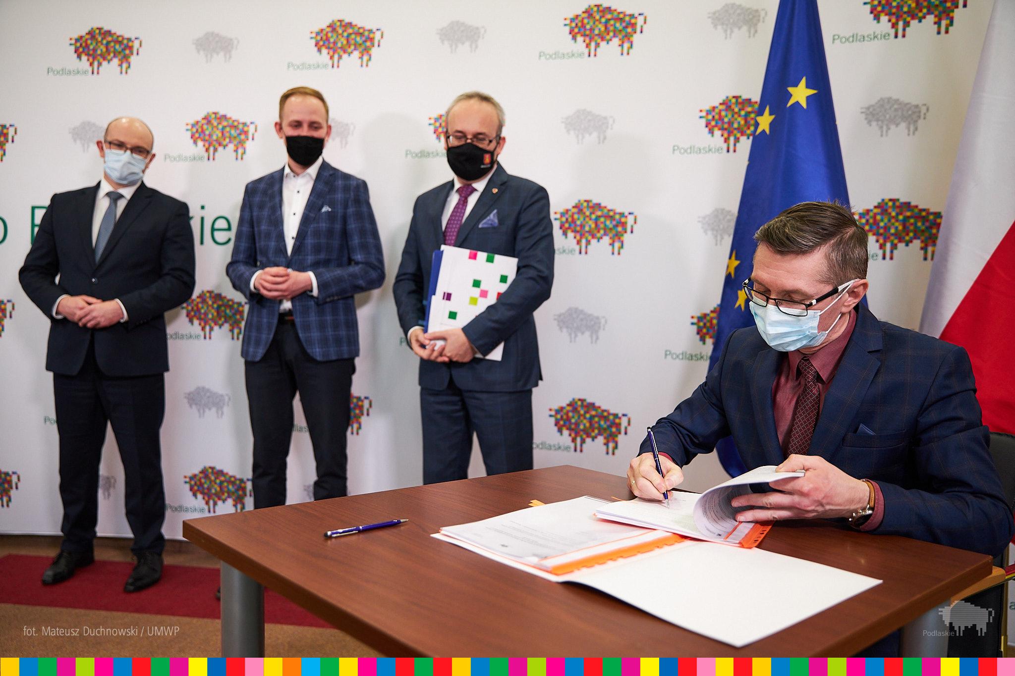 Mężczyzna podpisuje mowę. Na drugim planie stoi trzech mężczyzn na tle ścianki urzędu marszałkowskiego w Białymstoku. Za podpisującym mężczyzną znajduje się flaga Polski oraz Unii Europejskiej