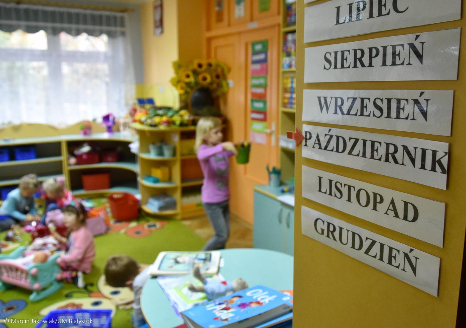 Dzieci bawią się w sali w przedszkolu. Po prawej stronie zdjęcia na ścianie przyczepione są kartoniki z nazwami miesięcy od lipca do grudnia