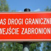 Czerwona tablica z białym napisem pas drogi granicznej wejście zabronione