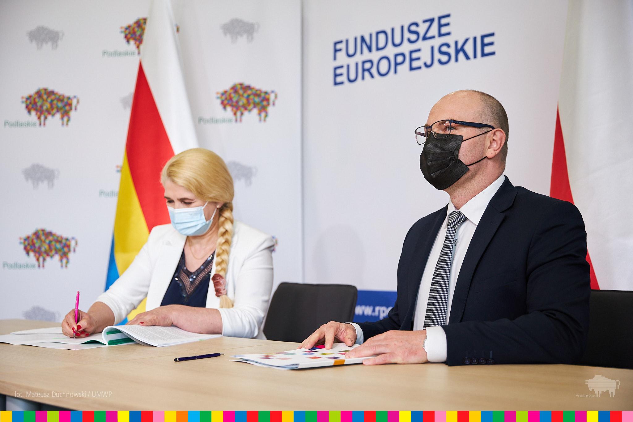"""Przy stole, od lewej strony siedzi kobieta i podpisuje umowę, z prawej mężczyzna, który patrzy przed siebie. Za nimi na ścianie jest napisane """"Fundusze Europejskie"""", ścianka województwa w żubry i flaga województwa: biało - czerwono - żółto - niebieska"""