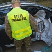 Funkcjonariusz POSG stoi przy samochodzie wypełnionym papierosami z przemytu