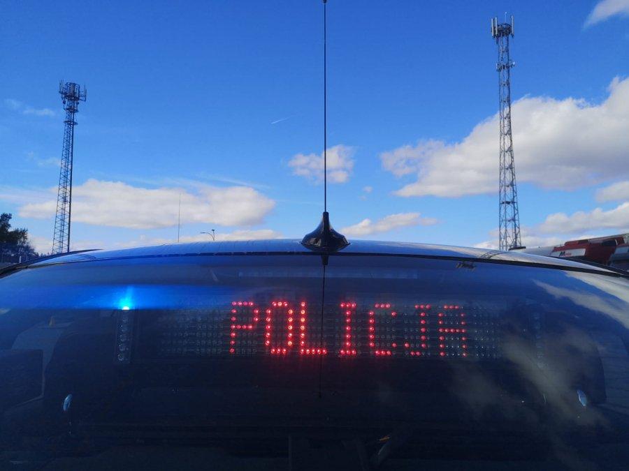 Nieoznakowany radiowóz policji, na tylnej szybie wyświetla się czerwony napis POLICJA