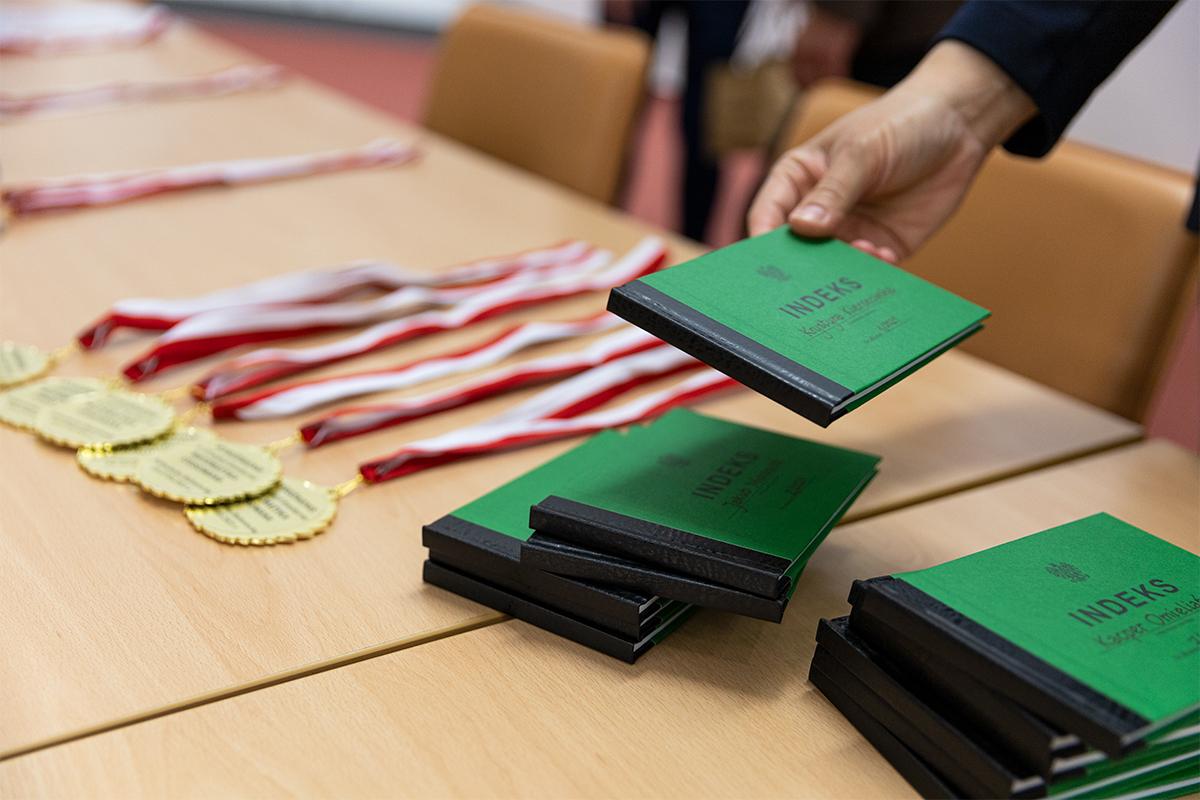 Na stole leżą medale oraz indeksy