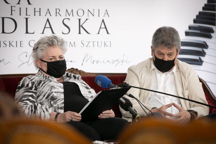 """Profesor Bielecka siedzi na kanapie, z lewej strony, po prawej jest maestro Błaszczyk. Za nimi znajduje się ścianka opery, widać część napisu: """"Opera i Filharmonia Podlaska"""" oraz fragment klawiatury fortepianu"""