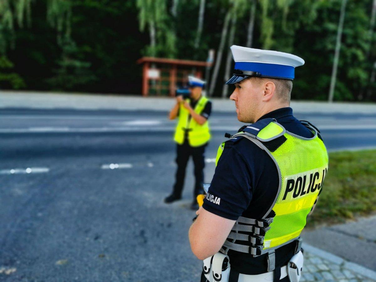 Dwaj policjanci przy drodze, jeden z nich trzyma w ręce miernik prędkości