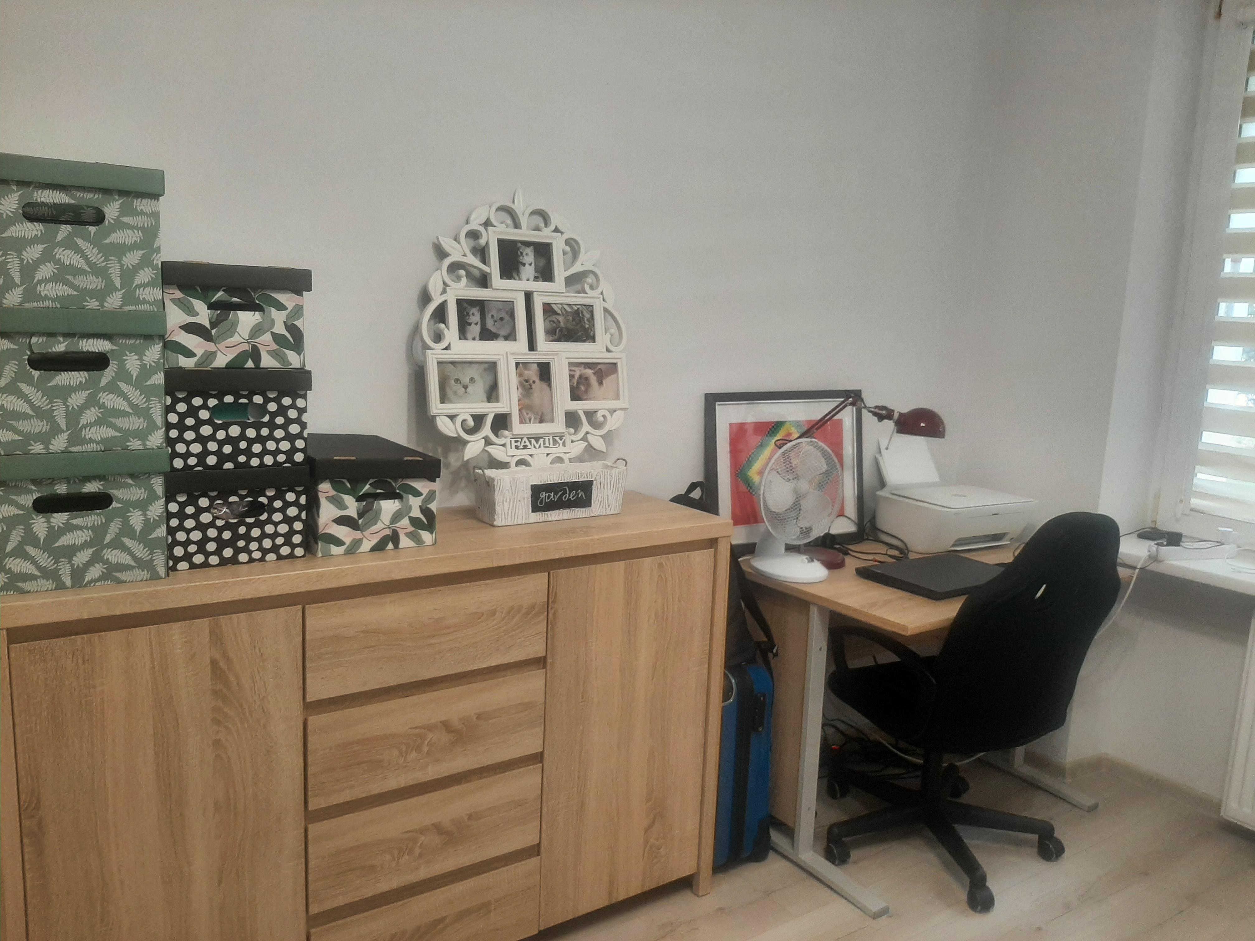 Pod ścianą stoi komoda, na której znajdują się kolorowe, tekturowe pudełka, białka ramka, w kształcie drzew, na którą składają się mniejsze rami, w które włożone są zdjęcia kotów. Obok komody toi biurko, przy którym stoi czarne krzesło a