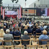 Tłum ludzi siedzi na krzesłach tyłem, a przodem do sceny, na której przemawia prezydent RP Andrzej Duda. Z prawej strony znajduje się telebim, na którym wyświetlona jest postać prezydenta Polski