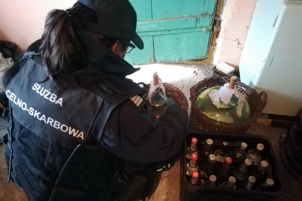 Funkcjonariuszka KAS przy zabezpieczonym alkoholu w butelkach i gąsiorach
