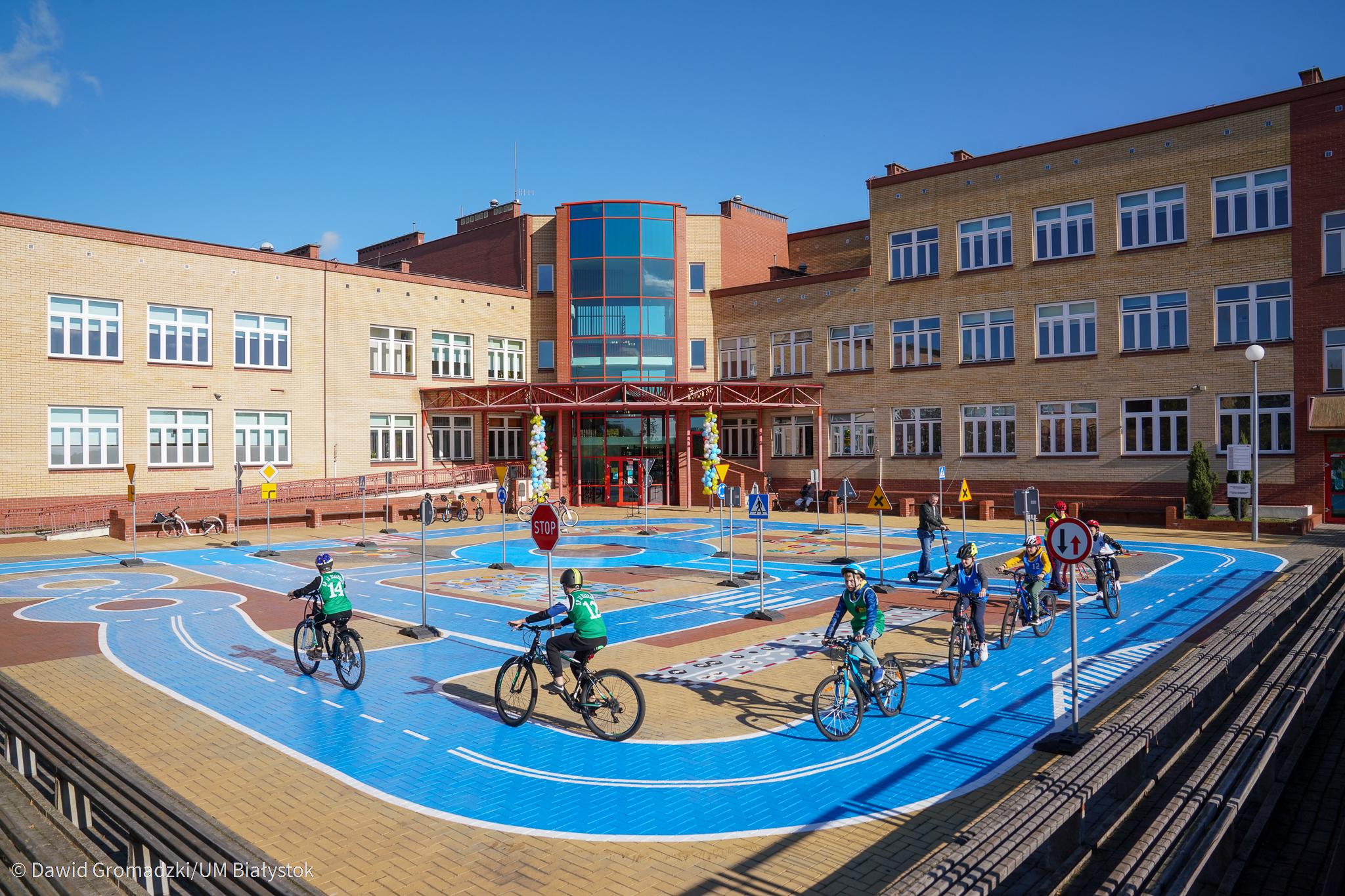Plac przed budynkiem szkoły, na którym urządzono miasteczko ruchu drogowego. Są niebieskie jezdnie, stoją znaki drogowe, na rowerach jeździ kilkoro uczniów