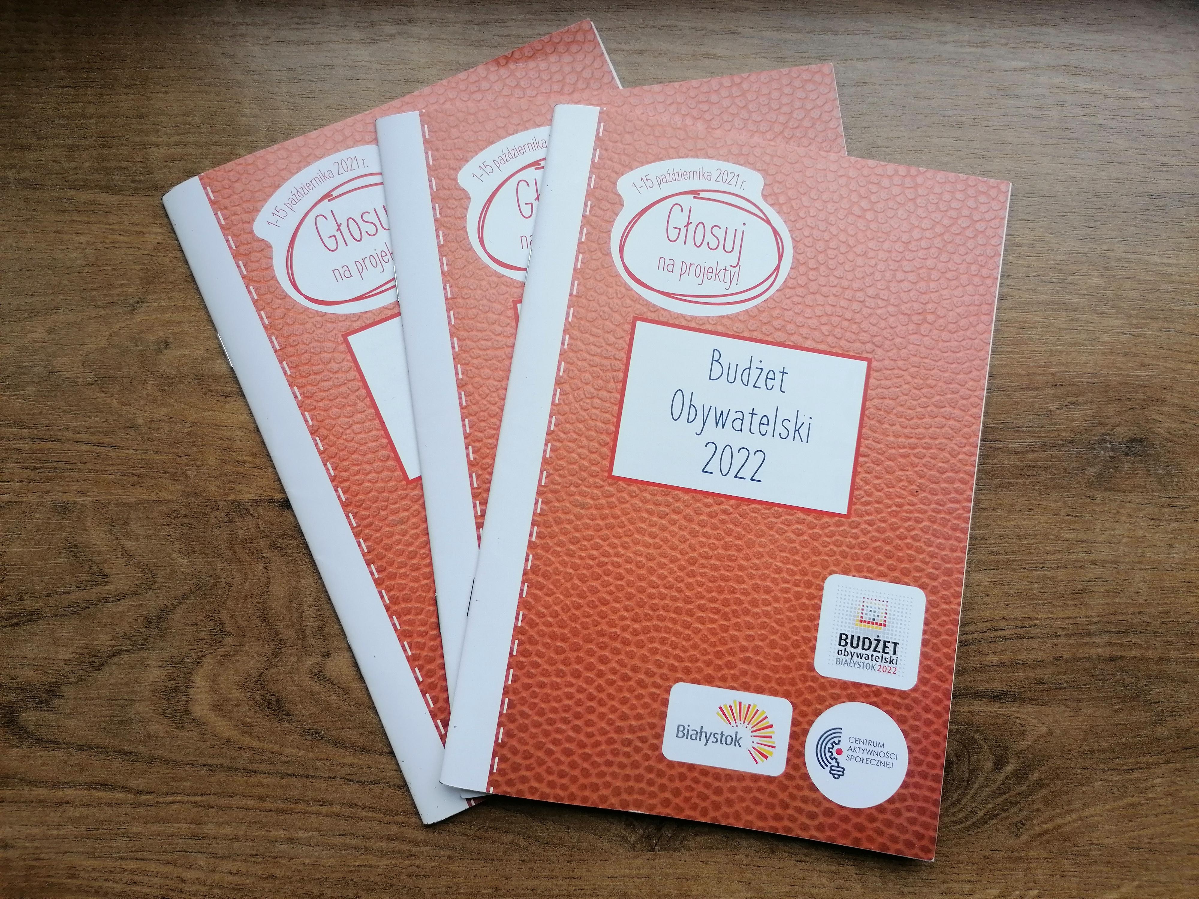 Na stole leżą trzy broszury informacyjne dotyczące budżetu obywatelskiego